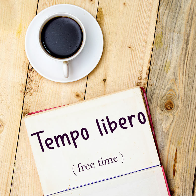 """cover image with the word """"tempo libero"""" and its translation written on a notepad next to a cup of cofee"""