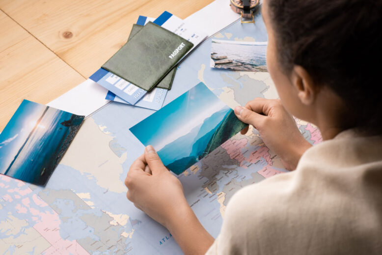 Over shoulder view of woman leaning on table with world map and watching photos while dreaming of travel