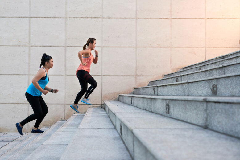 Female friends running up the stairs during morning training