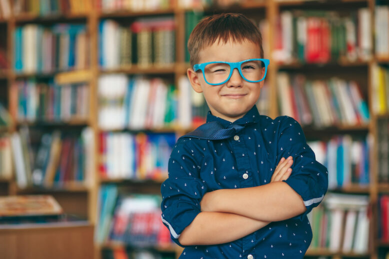 Smiling boy winking with blue glasses frame and blue tie on the shoulder on a book background.