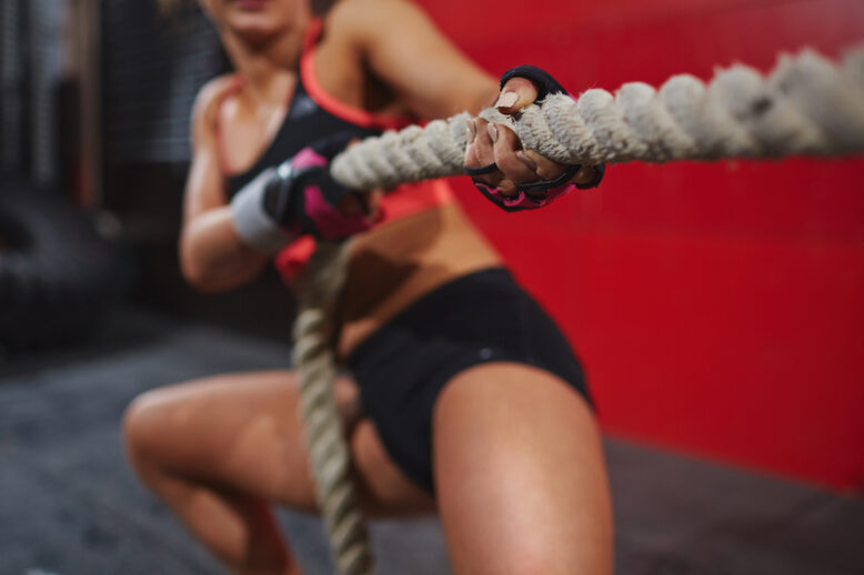Hands of strong woman pulling rope