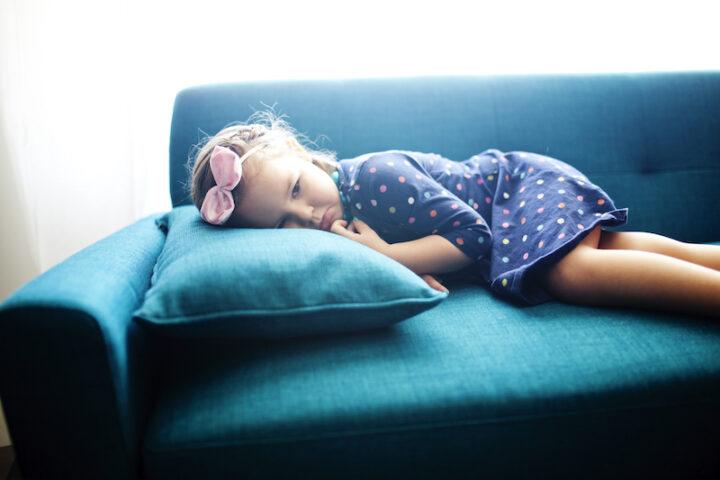 sad young girl lying on a blue sofa