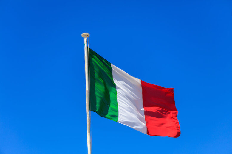Italy flag. Italian flag on a flagpole waving on a bright blue sky background