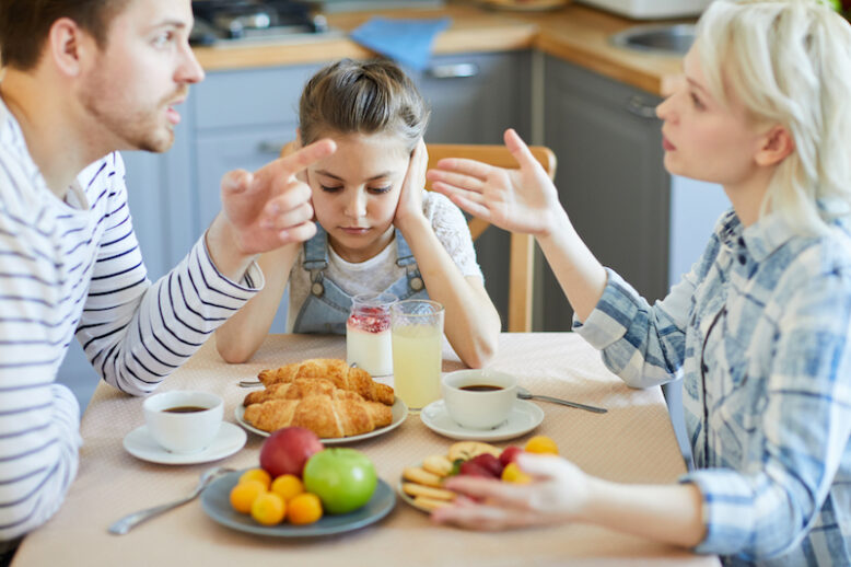 Young parents having argument by breakfast with their little daughter sitting near by