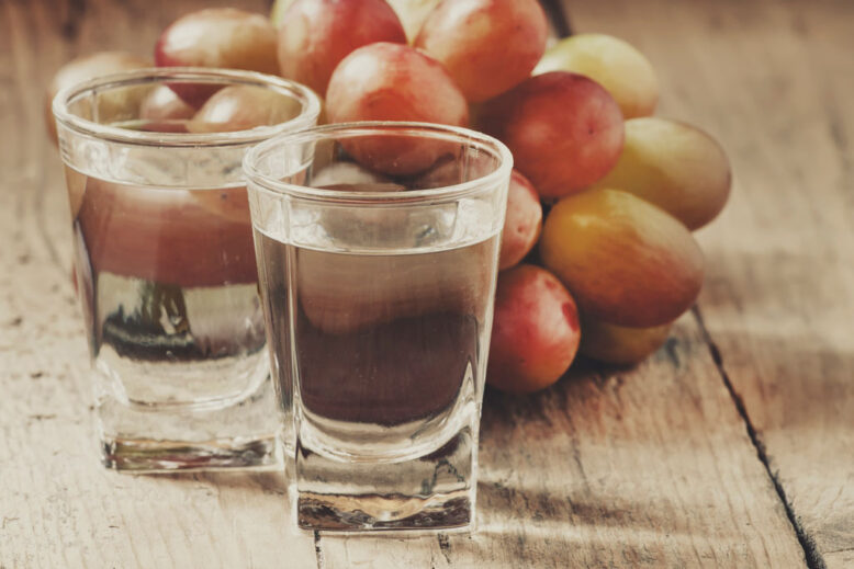 Grappa in small glass and ripe grapes on old wooden table, selective focus