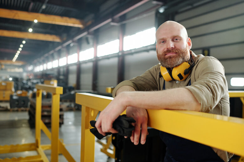 Portrait of content bald manual worker with beard holding work gloves and leaning on metal railings at factory