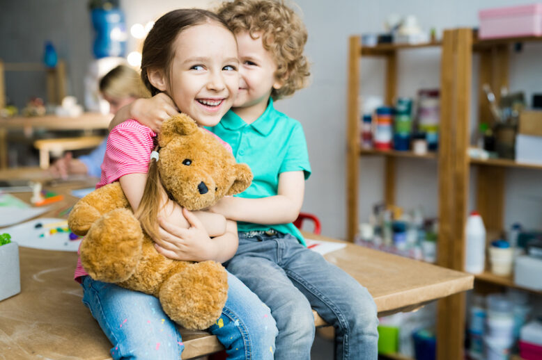Warm toned portrait of two cute little kids hugging and laughing happily holding teddy bear toy, copy space