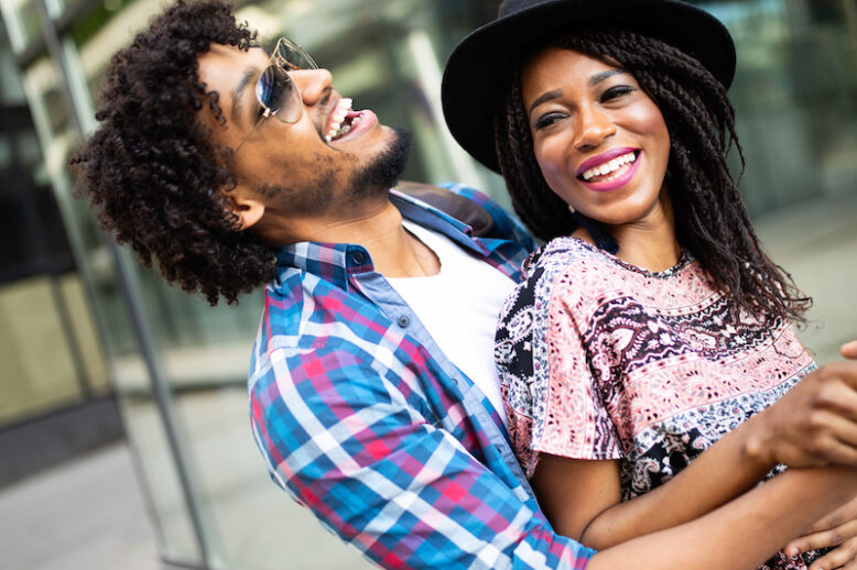 Happy young african couple hugging and laughing outdoors.