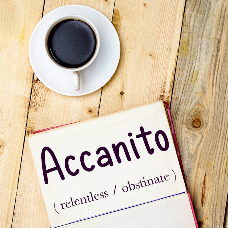 """cover image with the word """"accanito"""" and its translation written on a notepad next to a cup of cofee"""