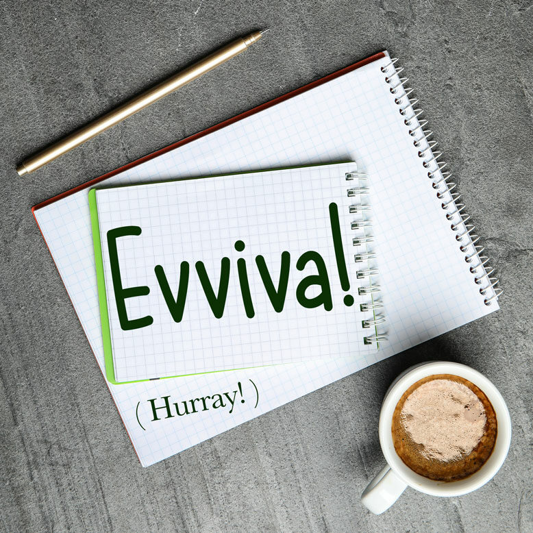 """cover image with the word """"evviva"""" and its translation written on a notepad next to a cup of cofee"""