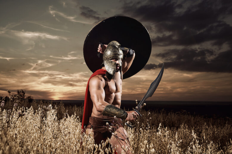 Sepia toned shot of a medieval roman warrior with gorgeous strong muscular ripped body walking through the field on dusk covering his back with a shield holding a sword