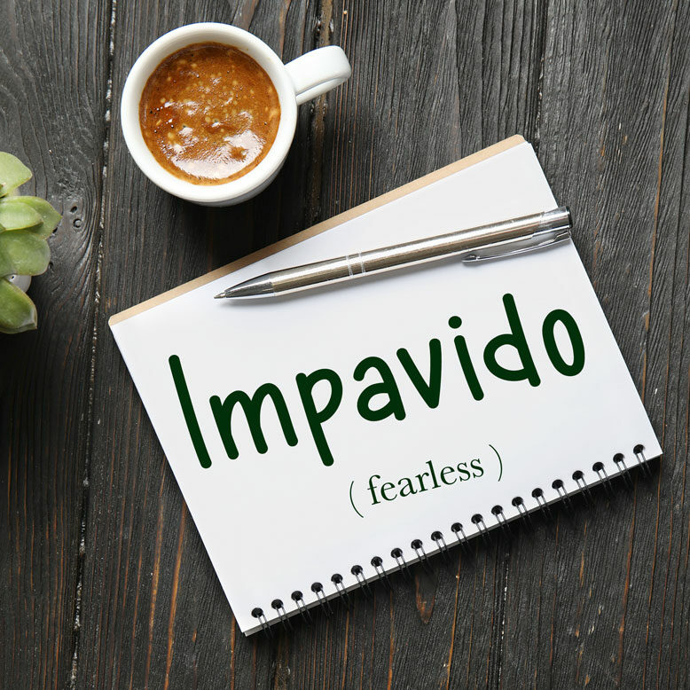 """cover image with the word """"impavido"""" and its translation written on a notepad next to a cup of cofee"""