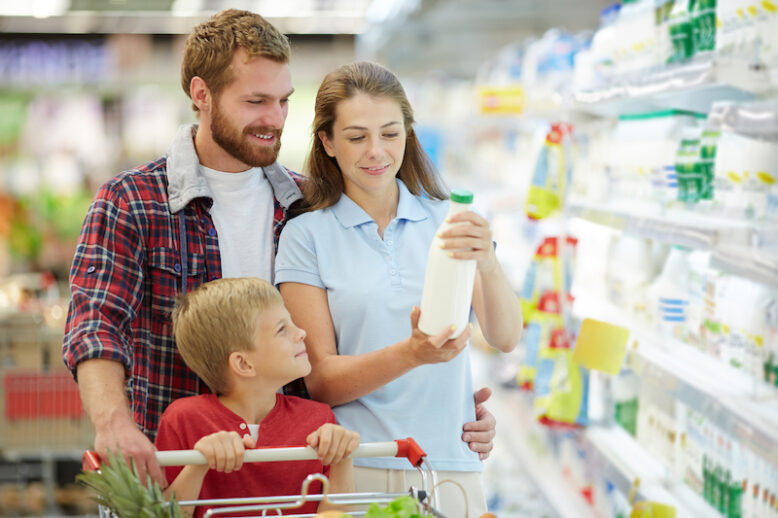 Young female and her family choosing milk in supermarket