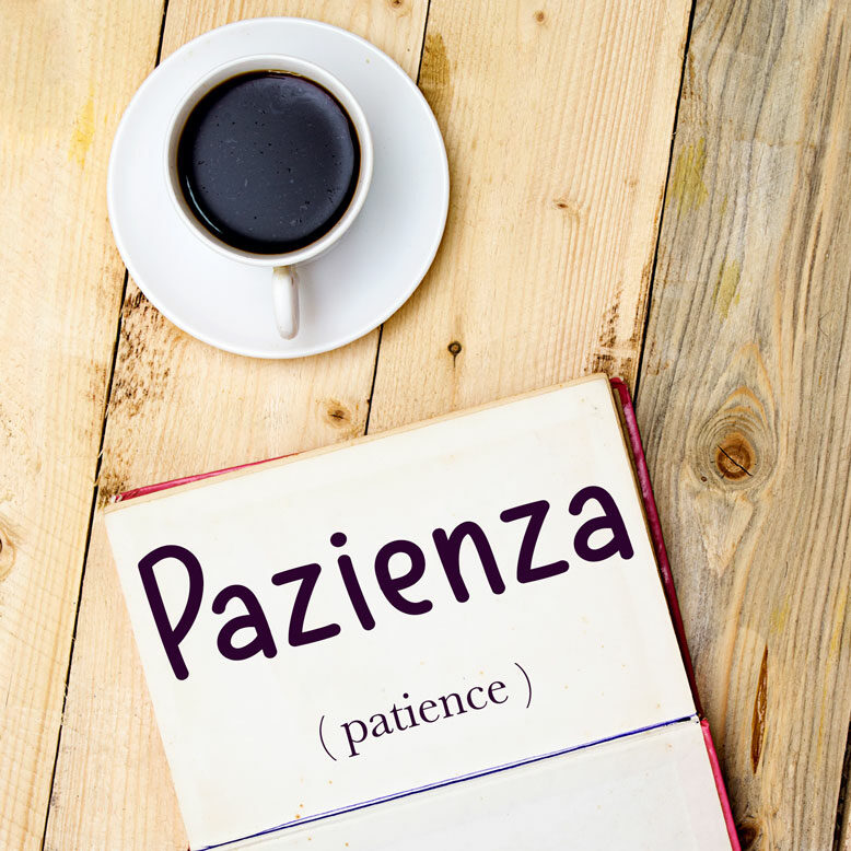 """cover image with the word """"pazienza"""" and its translation written on a notepad next to a cup of cofee"""