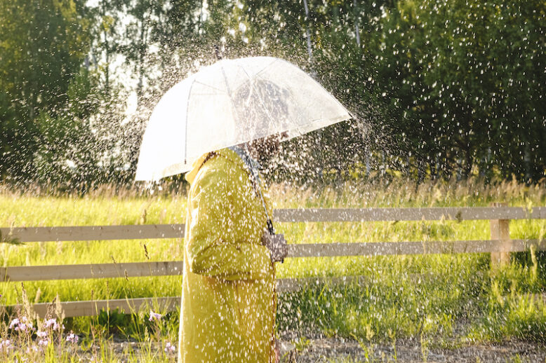 A man in a yellow raincoat in the rain. It's raining and the sun is shining