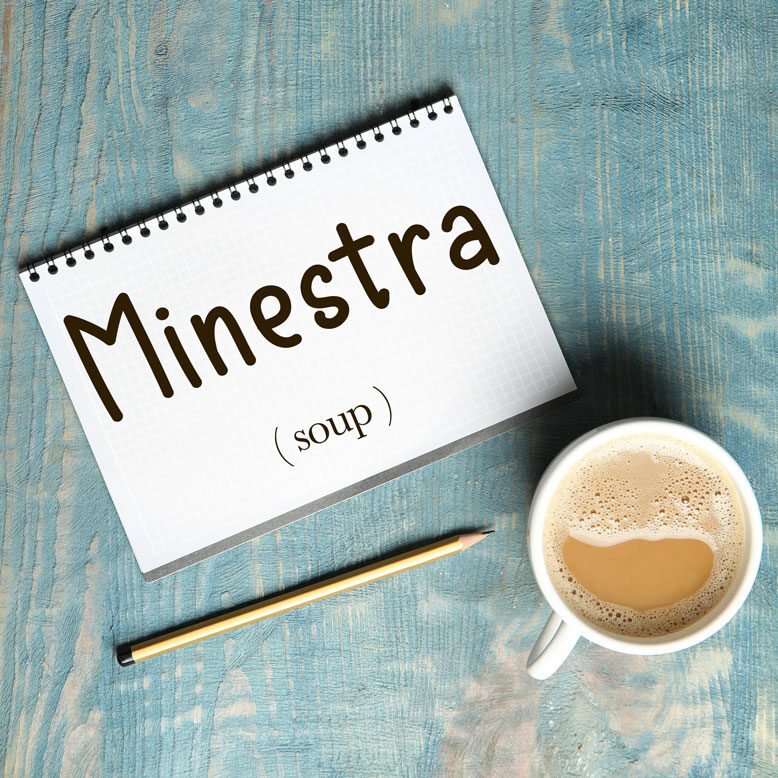 """cover image with the word """"minestra"""" and its translation written on a notepad next to a cup of cofee"""