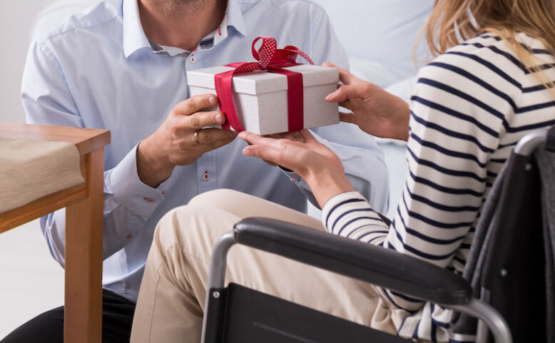 man giving a present to his wife sitting on a wheelchair