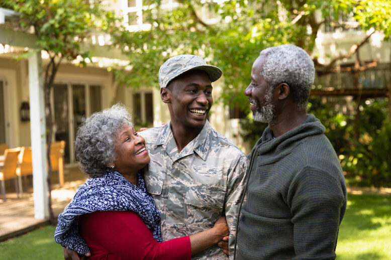 Front view of a young adult African American male soldier in the garden outside his home embracing and smiling with his parents