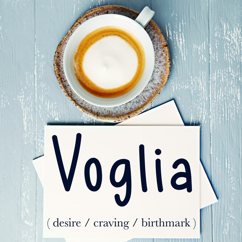 """cover image with the word """"voglia"""" and its translation written on a notepad next to a cup of coffee"""
