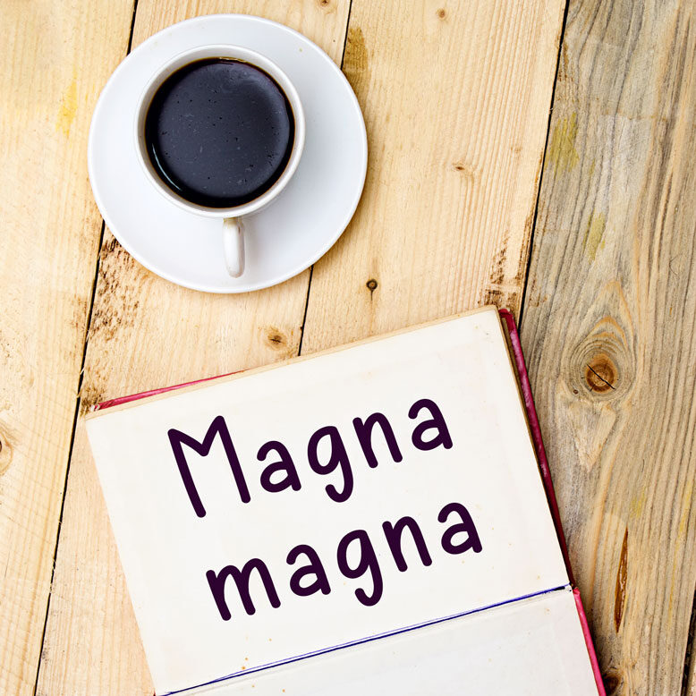 """cover image with the word """"magna magna"""" and its translation written on a notepad next to a cup of cofee"""