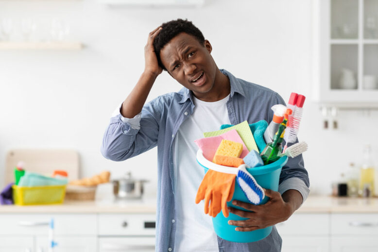 Confused black guy holding busket with cleaning tools and touching his head, unwilling cleaning house