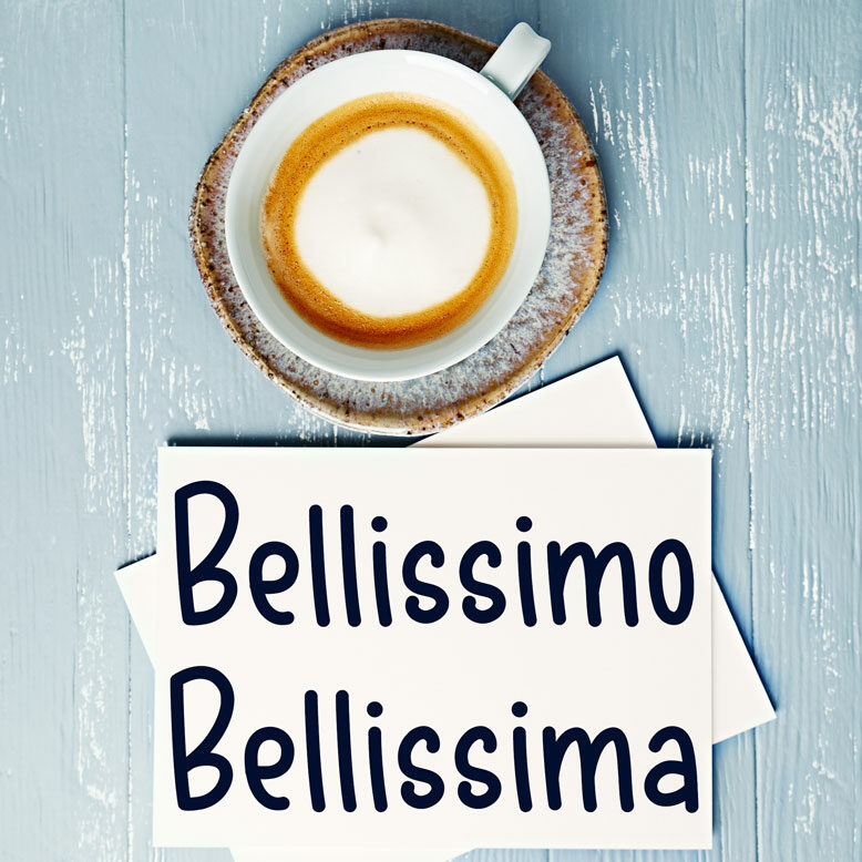 """cover image with the word """"bellissimo"""" and """"bellissima"""" written on a notepad next to a cup of cofee"""