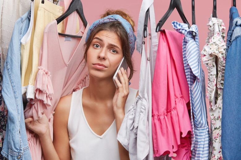 Nothing to wear concept. Beautiful young woman dressed casually feeling frustrated standing among multicolored clothes in her wardrobe, speaking on mobile phone with friend, asking for advice
