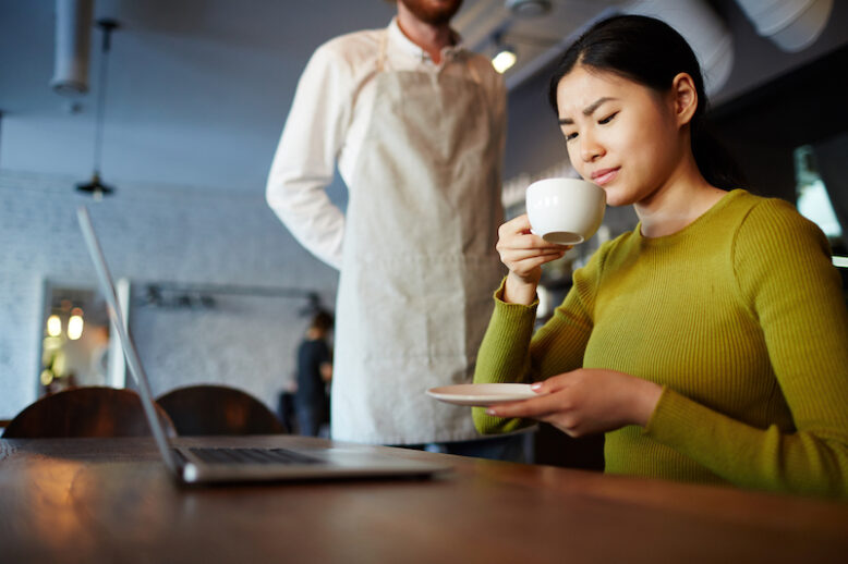 Asian woman drinking coffee in front of her laptop, looking unsatisfied with the taste of the drink. A waiter waits in the background.