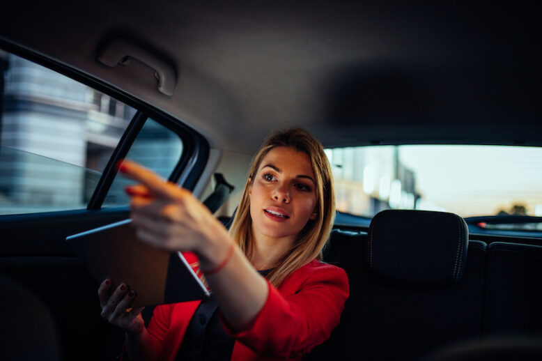 Attractive businesswoman showing the direction to her driver.