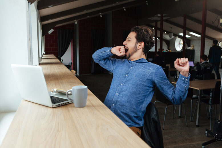 Man sitting at the table with laptop computer and yawning in cafe