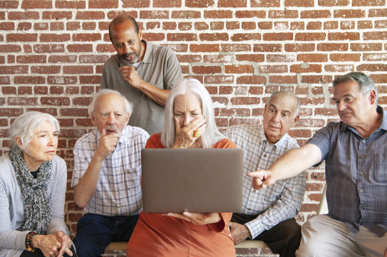 Group of elderly people using a laptop