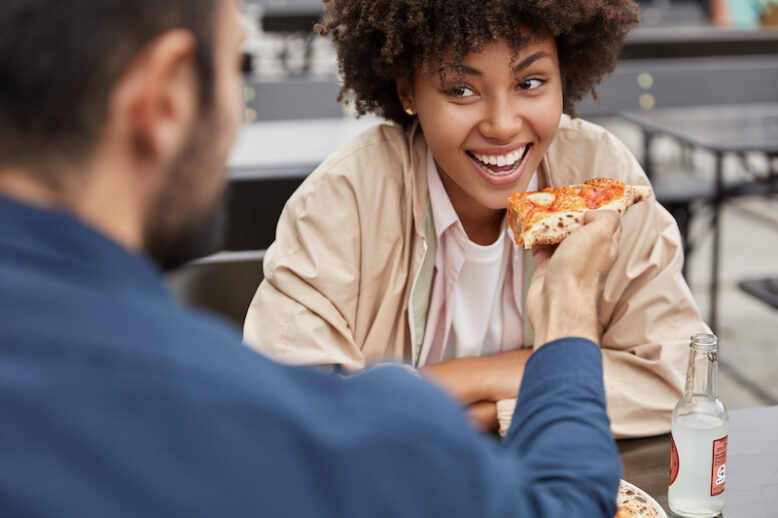 cheerful black woman with Afro hairstyle eats delicious Italian pizza from boyfriends hands who feeds her in outdoor cafeteria