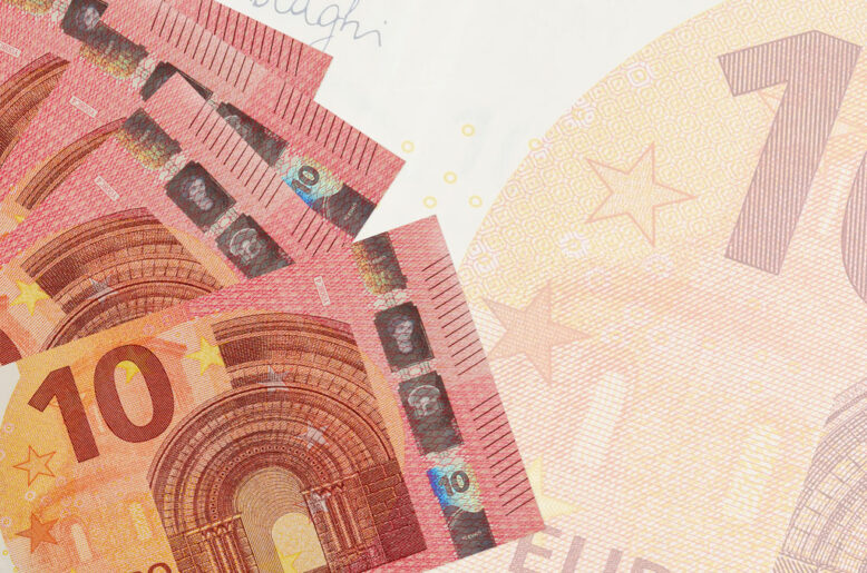 10 euro bills lies in stack on background of big semi-transparent banknote.