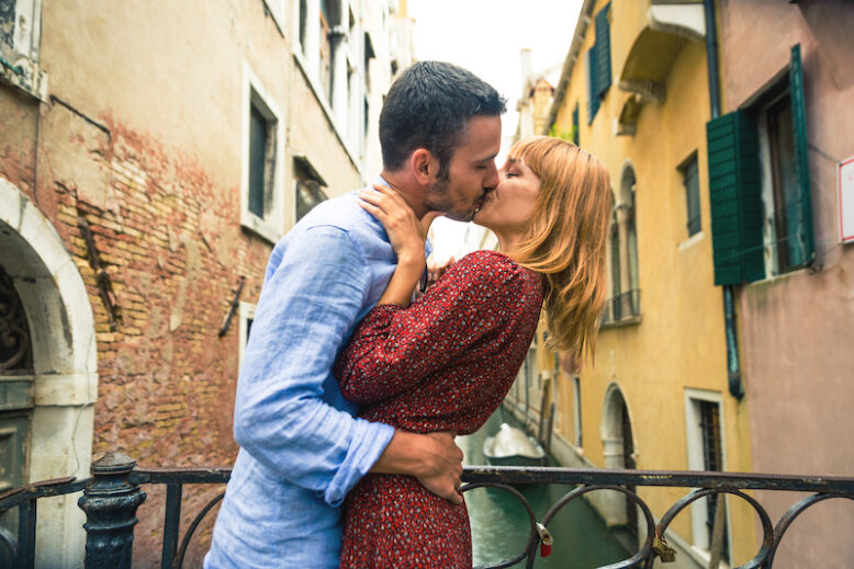 Beatiful young couple having fun while visiting Venice - Tourists travelling in Italy and sightseeing the most relevant landmarks of Venezia