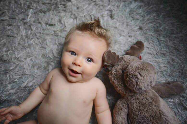 cute baby next to a stuffed toy