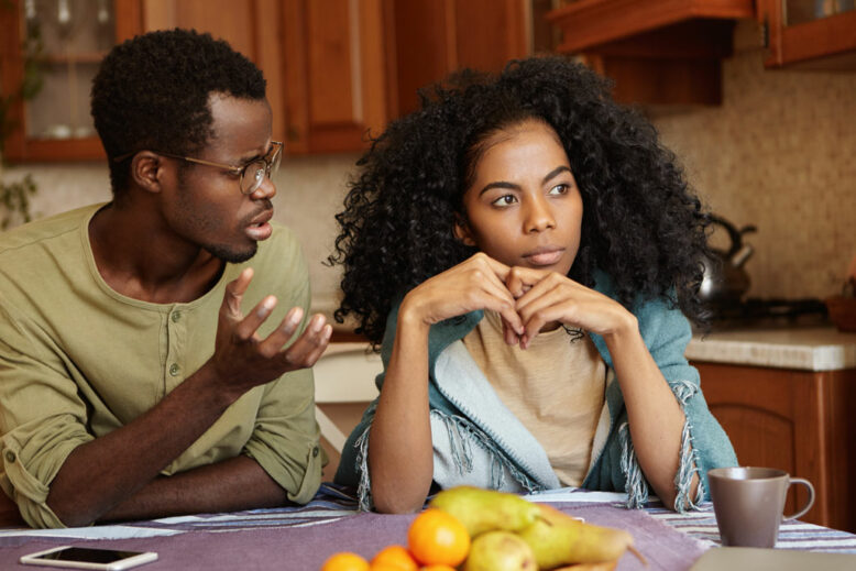 Indignant depressed young Afro-American male in glasses trying to have conversation to his indifferent wife who cheated on him.