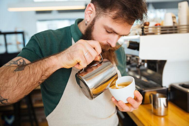 Barista making cappuccino in coffee shop