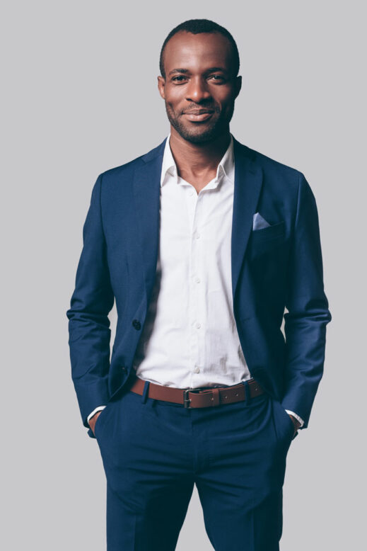 Handsome young African man in smart casual jacket holding hands in pockets and smiling while standing against grey background