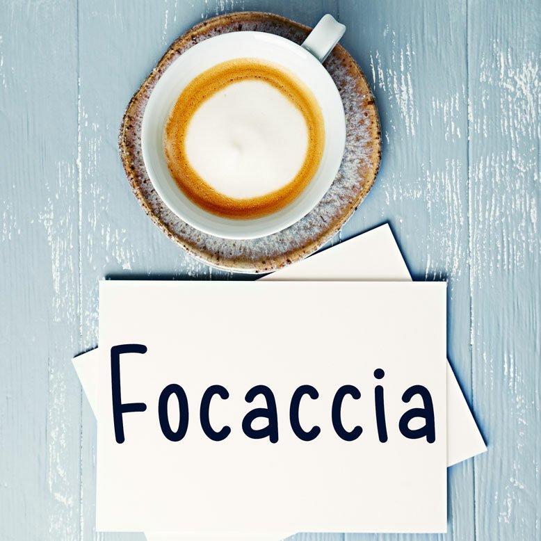 """cover image with the word """"focaccia"""" and its translation written on a notepad next to a cup of cofee"""