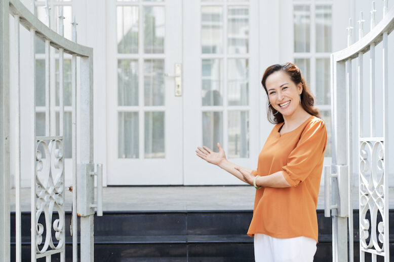 Happy mature Asian woman inviting you to enter her house