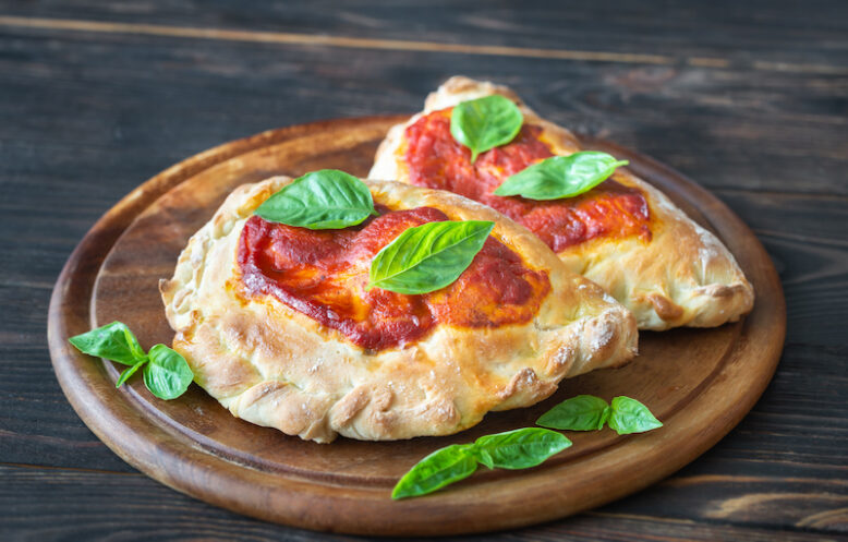 Homemade calzone stuffed with pancetta and mushrooms on the wooden board