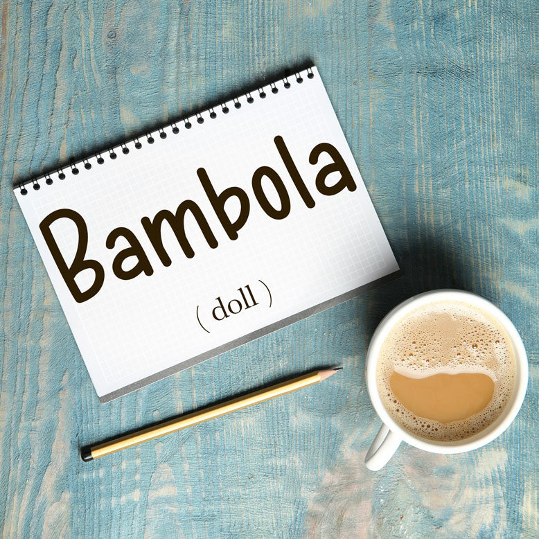 """cover image with the word """"bambola"""" and its translation written on a notepad next to a cup of cofee"""