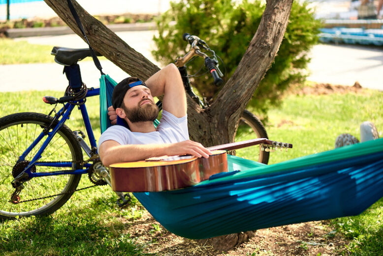 A young man with a guitar sleeps in a hammock on a summer day in the park.