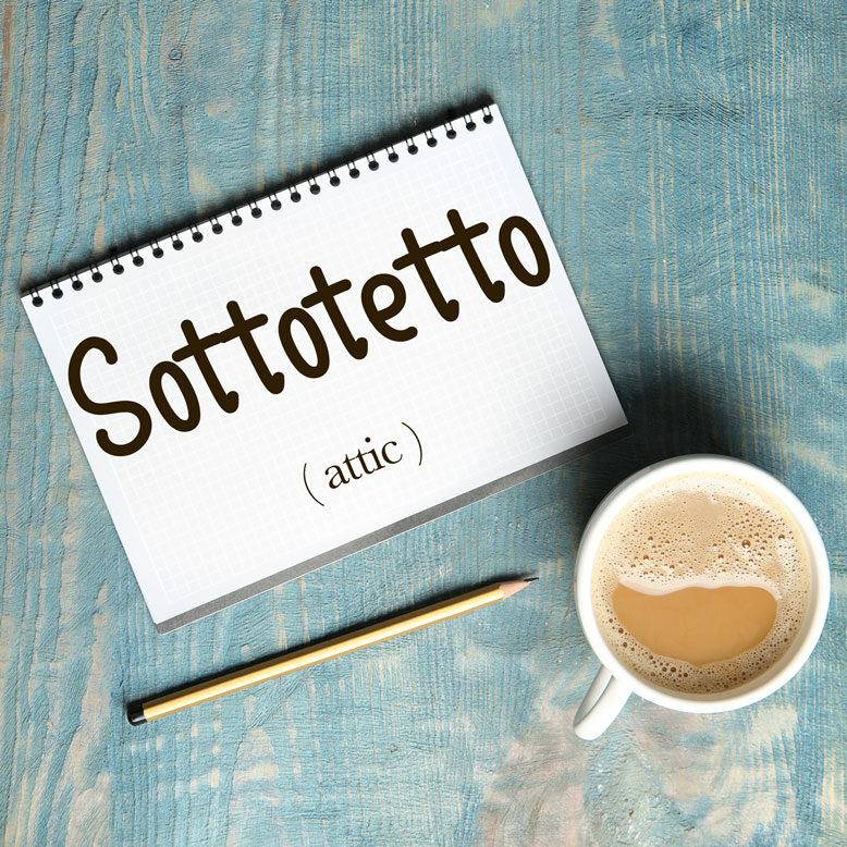 """cover image with the word """"sottotetto"""" and its translation written on a notepad next to a cup of cofee"""