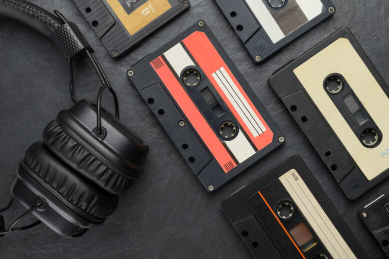 Black on-ear headphones and audio tape compact cassettes on slate background
