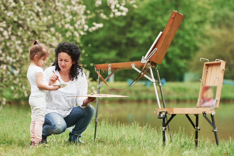 Grandmnother teaching granddaughter how to paint in the natural parkland