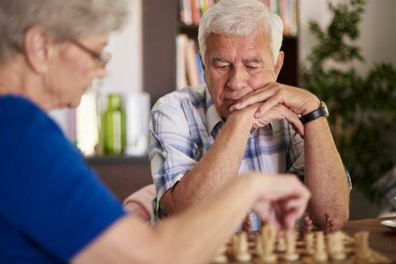 elderly couple playing chess in the living room
