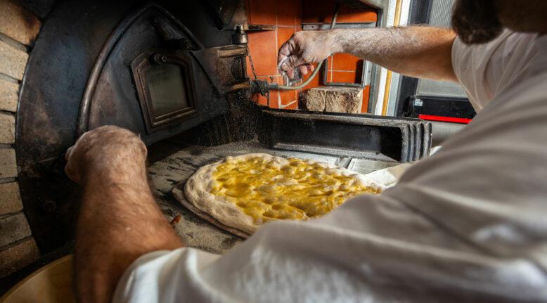 baker making the schiacciata all'olio, one of Tuscany's top bakery treats.