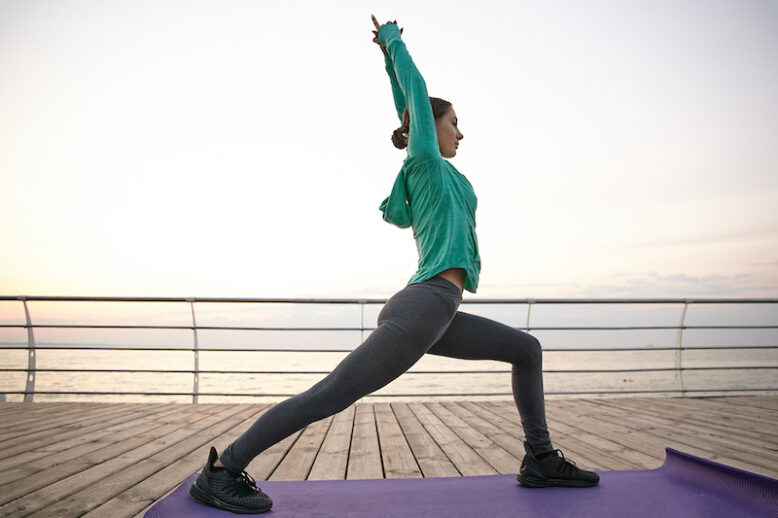 Slim sporty young woman in yoga pose, dressed sport wears