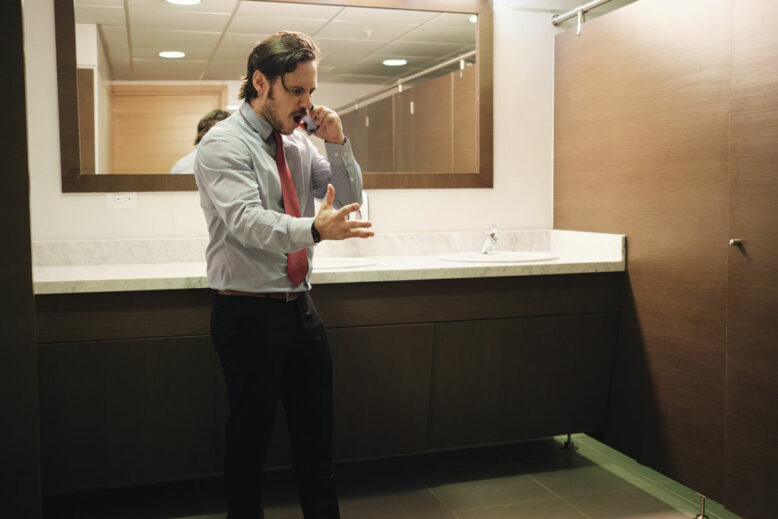 Angry man using corporate restroom while talking on cell phone